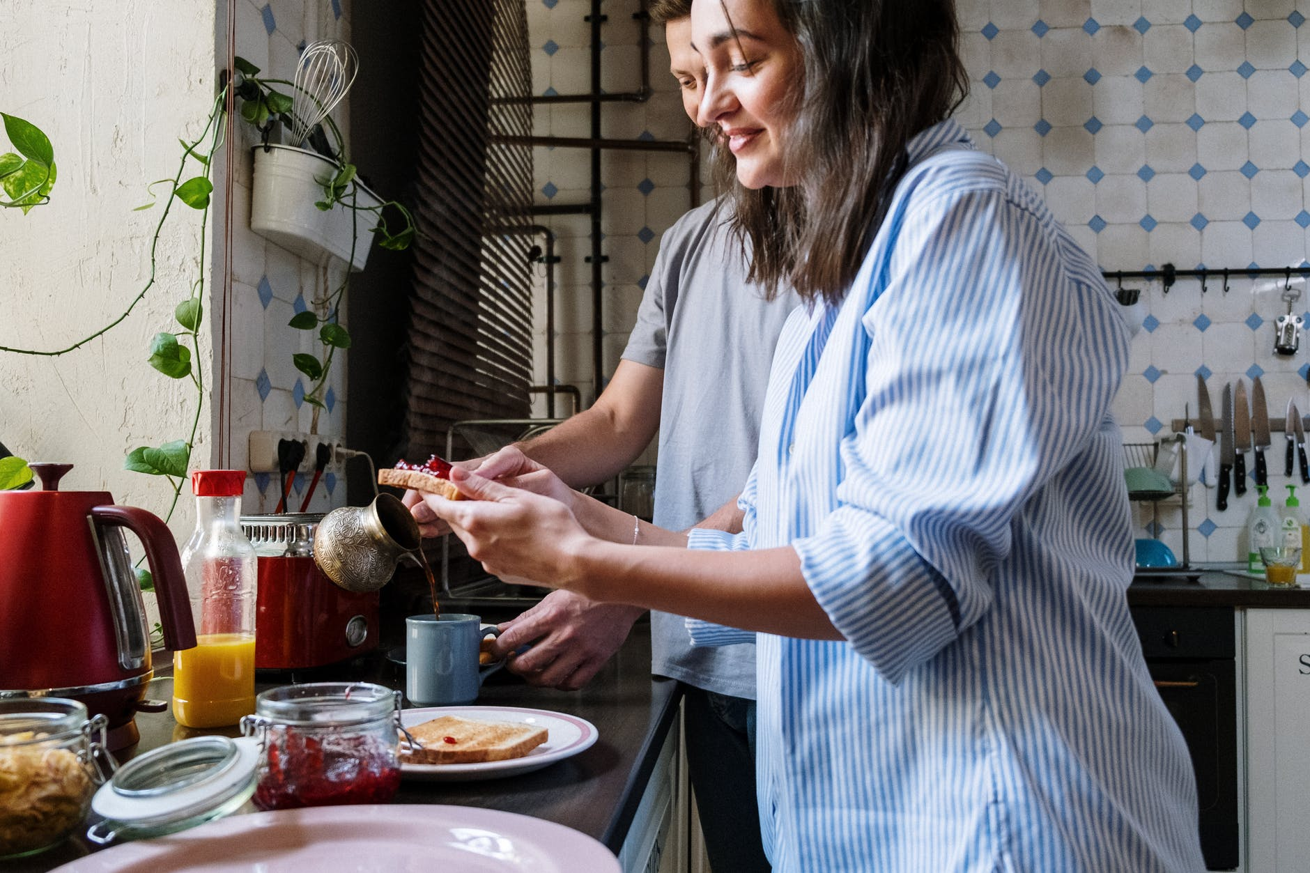 woman in blue and white stripe shirt holding red food