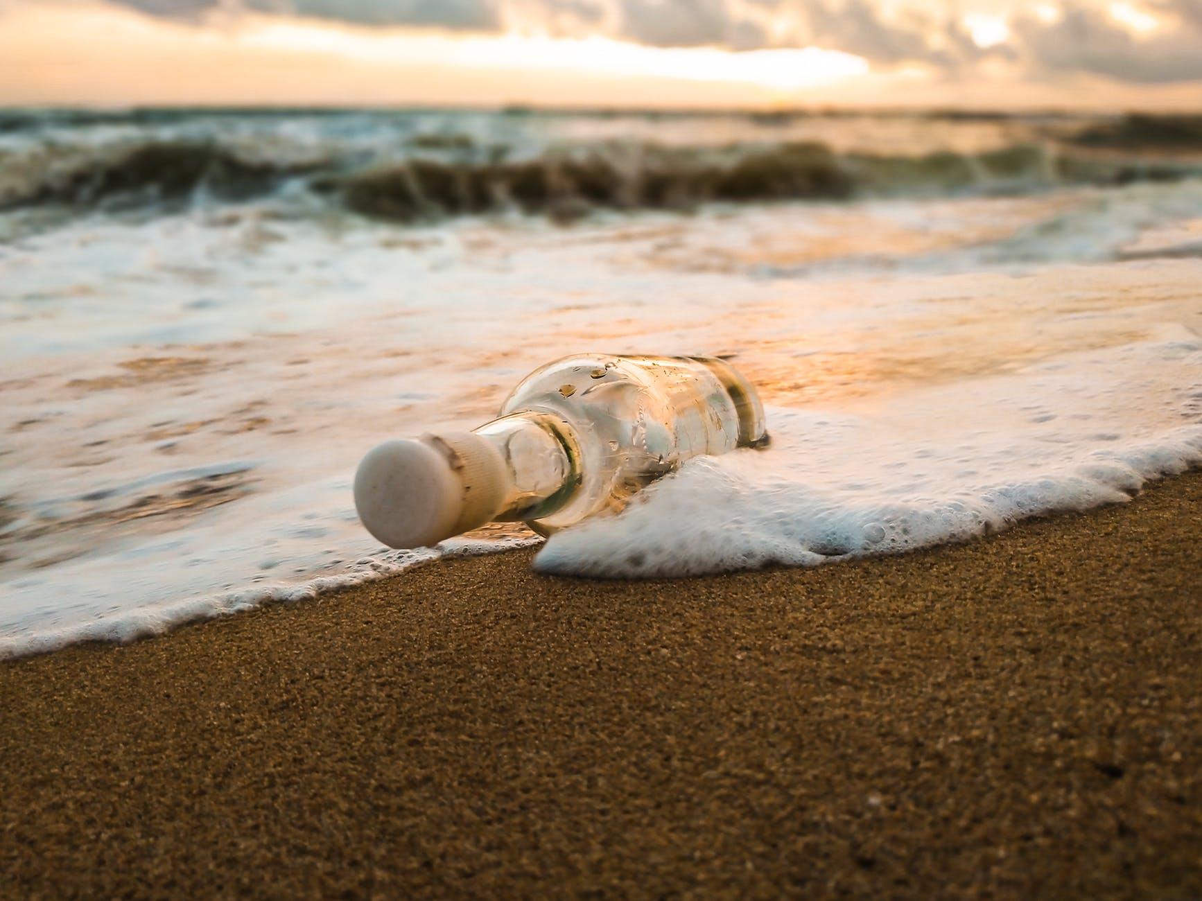 glass bottle on empty sandy beach