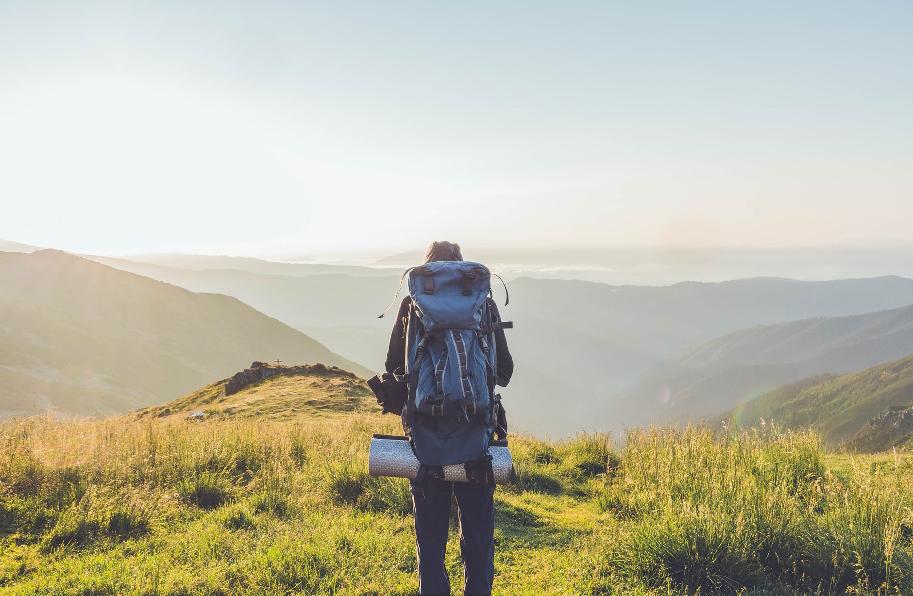unrecognizable male traveler standing on hill against misty scenic highlands